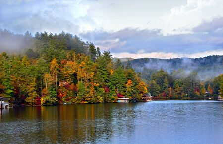 lake house: Colorful shoreline in autumn on a quiet lake. Stock Photo