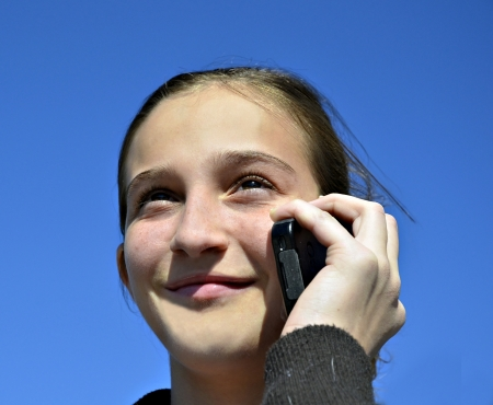 Beautiful preteen girl talking on a cell phone with blue sky background.