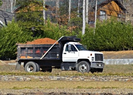 A large dump truck on a road hauling a load of dirt