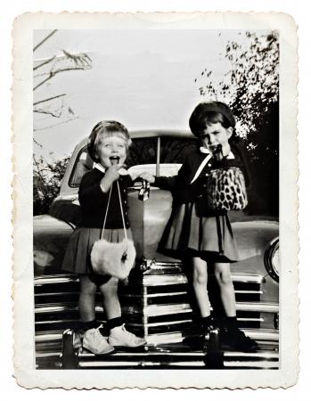 Twee zussen op de voorkant van een auto die met leuke uitdrukkingen, retro foto uit 1950 Stockfoto