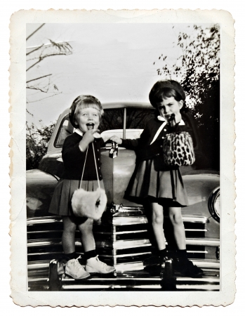 old people: Two sisters on the front of a car posing with cute expressions, retro photo from 1950  Stock Photo