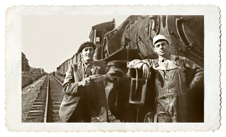 olden: A vintage snapshot of two men standing at an old engine.