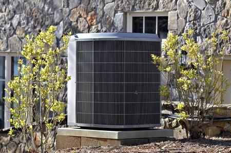 aire acondicionado: Una unidad de acondicionador de aire en el lado de una casa.