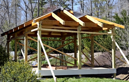 Constructing a covered wooden deck area on the back of an existing home  The flooring is a composite material  photo