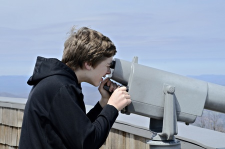 A young boy on Brasstown Bald looking at the view with a telescope. photo