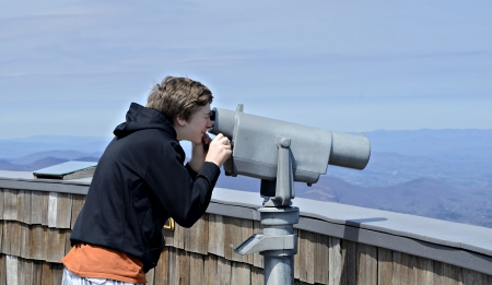overlook: A young boy on Brasstown Bald looking at the view with a telescope.