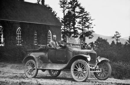 old photograph: Two smiling men in an old convertable truck.