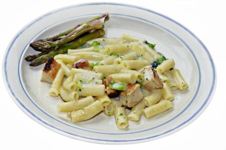 alfredo: A meal of chicken, pasta and broccoli in alfredo sauce with fresh organic asparagus on a plate  Stock Photo
