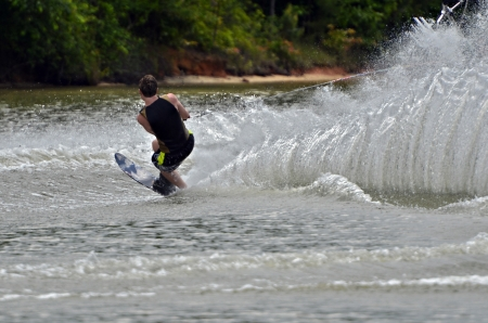 A young boy cutting across a wake during a waterski competition  Imagens