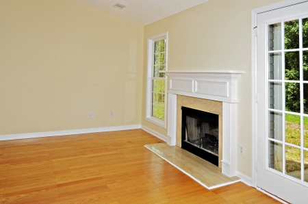 den: Wood burning fireplace in a room with oak floors flanked by a window and a french door  Stock Photo