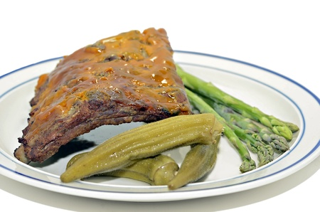 A plate of barbecued ribs with fresh asparagus and pickled okra  photo