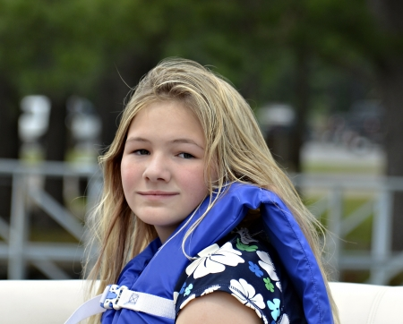 life jackets: Young girl with life vest on a boat