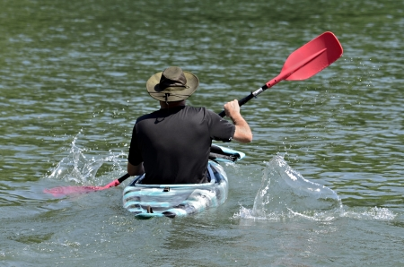 kayaker: A man in a kayak splashing and paddling.