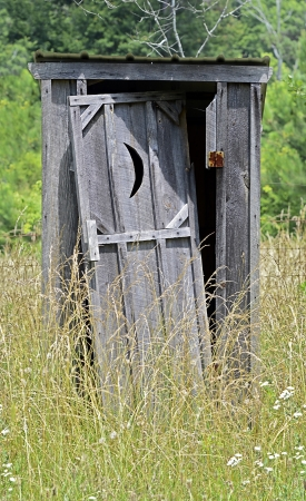 An old outhouse with door falling off surrounded by weeds