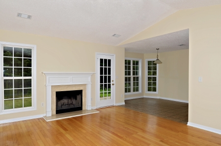 Wood burning fireplace in a greatroom with oak floors flanked by a window and a french door. Stock Photo