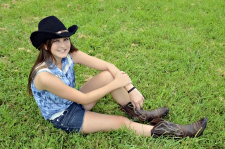 A young teenager with western hat and boots sitting in the grass smiling. photo