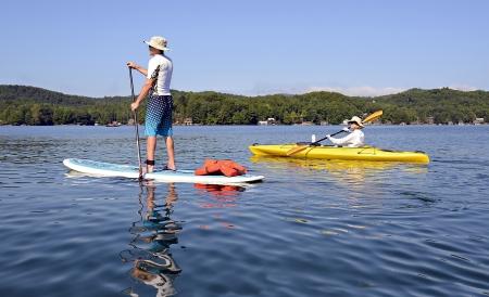 남자와 아내가 함께 운동을 받고 외륜선과 아름 다운 호수에 카약. 스톡 콘텐츠