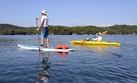paddle: A man and wife getting exercise together paddleboarding and kayaking on a beautiful lake.