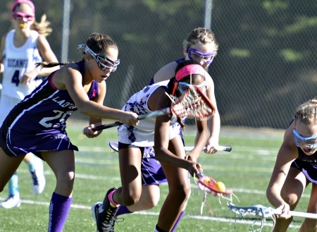 CUMMING, GA, USA - OCTOBER 20: Young girls playing Lacrosse October 20, 2013, in Forsyth, GA, the Lady Raiders vs the Titans. Running for the ball.