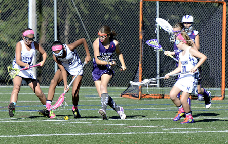 titans: CUMMING, GA, USA - OCTOBER 20: Young girls playing Lacrosse October 20, 2013, in Forsyth, GA, the Lady Raiders vs the Titans. A battle for the ball at the goal.