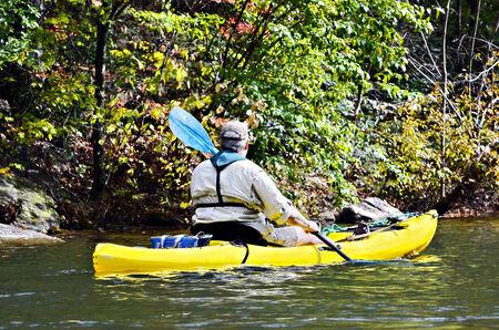 man kayaking along the shoreline of a lake