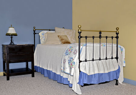 Twin iron and brass bed on walls painted contrasting colors with copy space above the bed area.