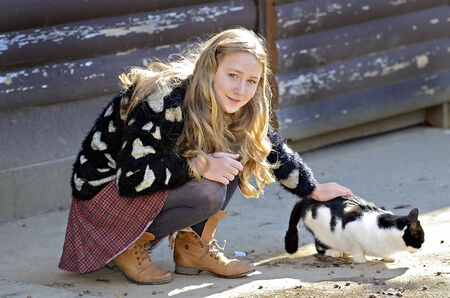 A pretty young girl petting a barn cat while it eats  photo