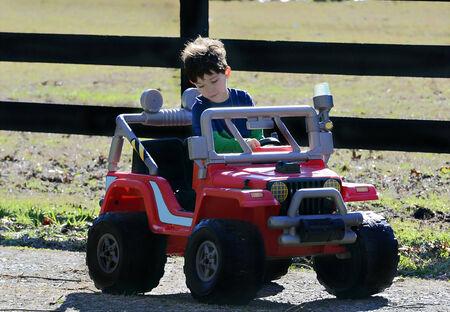 Een jonge jongen met plezier rijden zijn speelgoed auto buiten