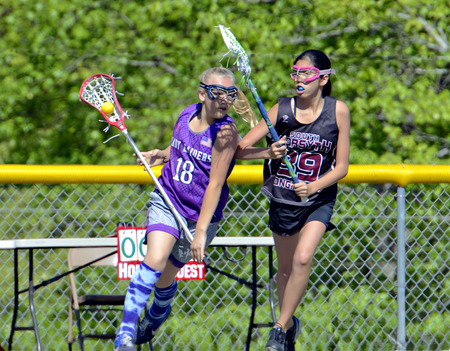CUMMING, GA, USA - April 26  Young girls playing Lacrosse April 26, 2014, in Cumming, GA, the Lady Raiders vs the Longhorns  Running with the ball