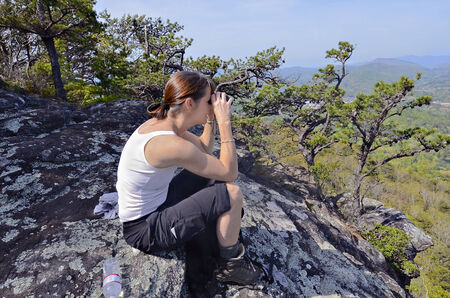 A woman hiker on a rock overlook using her binoculars   Cell phone on her pocket  Banco de Imagens