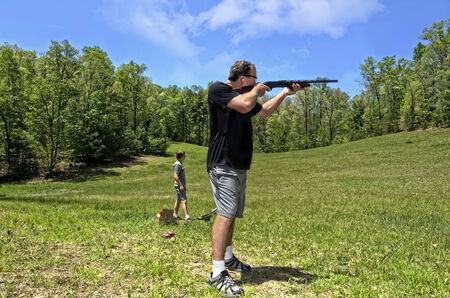 A man and his son shooting clay targets in a field