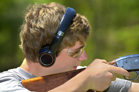 A young teenager learning to shoot targets with a shotgun