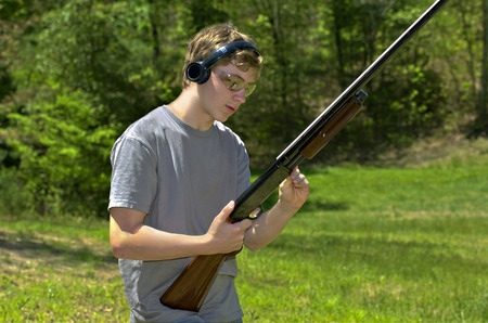 rifle: A young teenager loading a shotgun getting ready to practice shooting targets  Stock Photo