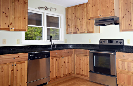 A small kitchen area with knotty pine cabinets and Bamboo floors