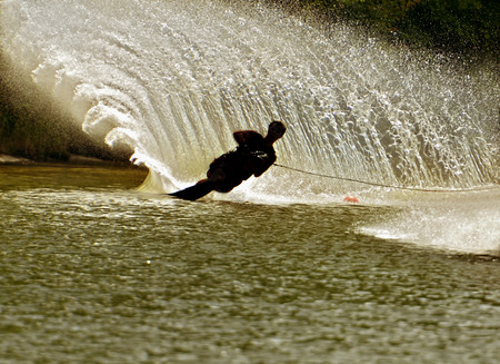 Silhouette of a boy siking in front of a large rooster tail spray