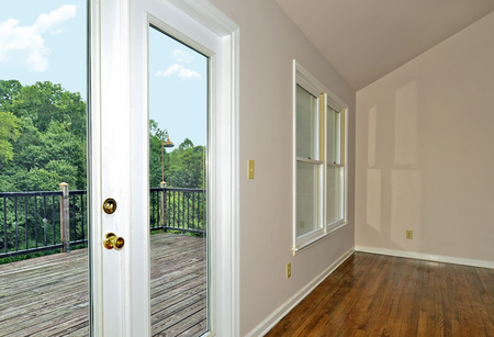 sheetrock: Interior of a great room showing the french doors, windows and deck outside.