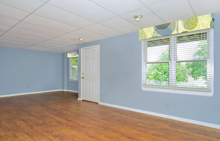 drop ceiling: A colorful basement room with drop ceiling, hardwood floors, windows and a door.