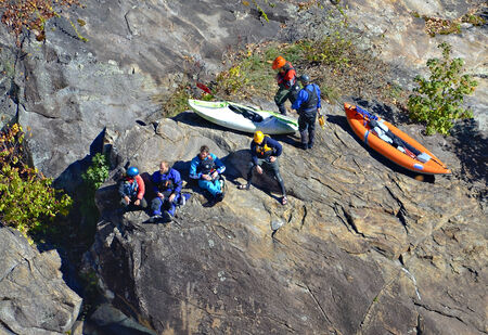 TALLULAH FALLS, GA, USA - NOVEMBER, 2- A group of kayakers resting on a rock and watching others after a run down the rapids in the Tallulah River Gorge, November 2, 2014.