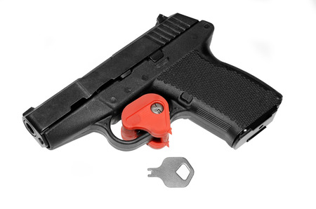 safety: A pistol that has the trigger locked with a key.  A firearm safety feature. Stock Photo