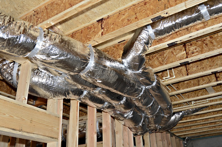 A basement ceiling in a new construction showing the heat/air duct work attached to the framework with PVC pipes in the background.