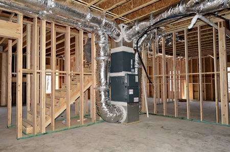 The newly framed basement area of a house. The central heat and air duct work system is beside the stairs.