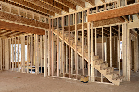 The interior of a home under construction showing the stairs, bedroom or office and bath areas. Stock Photo