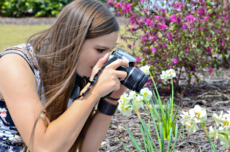 taking photograph: A teenager taking a photograph of her garden flowers. Stock Photo