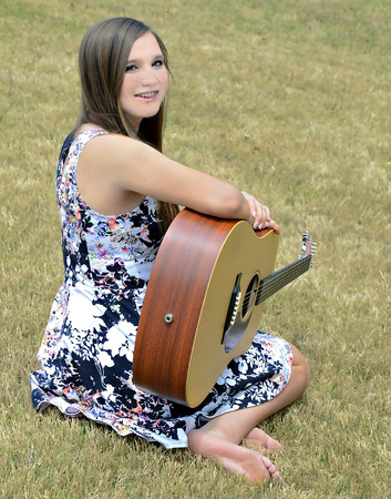 A beautiful young girl, with braces, outdoors with a guitar. Stock Photo