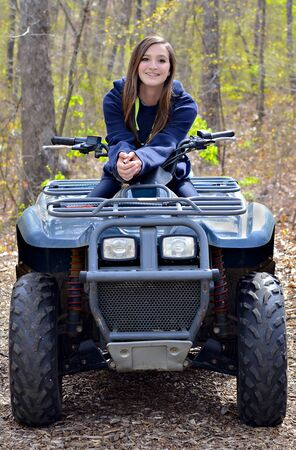 four wheeler: Beautiful teenager, with braces, on a four wheeler trail in the woods. Stock Photo
