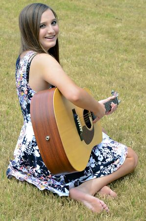 A beautiful young teen girl outdoors with a guitar. Stock Photo