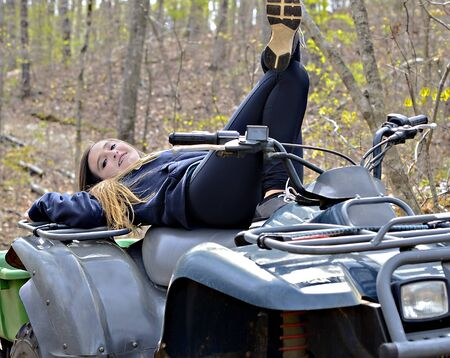 A beautiful young teen having a fun day with her 4-wheeler in the woods. photo