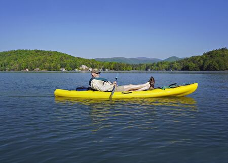A retired gentleman resting in his kayak and enjoying the mountain lake. Stock Photo