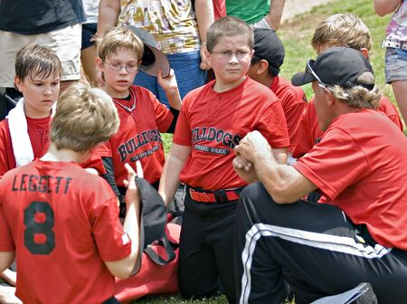 team mate: A coach talking to his little league baseball team, families are in the background listening.