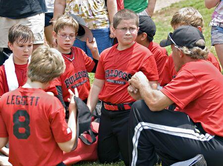 padres hablando con hijos: Un entrenador de hablar con su pequeño equipo de béisbol de la liga, las familias están en la escucha de fondo.